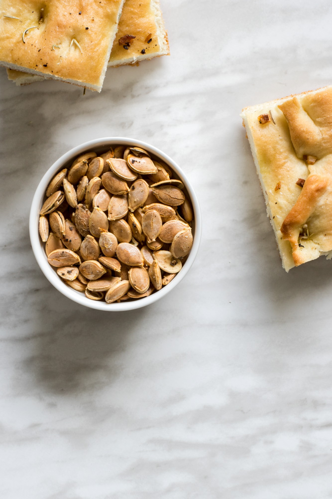 Roasted pumpkin seeds and pieces of rosemary bread.