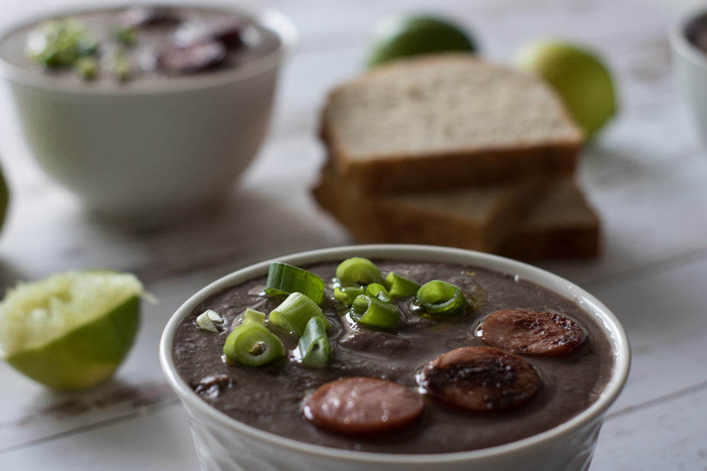 Bacon black bean soup with bread, green onions and sausage