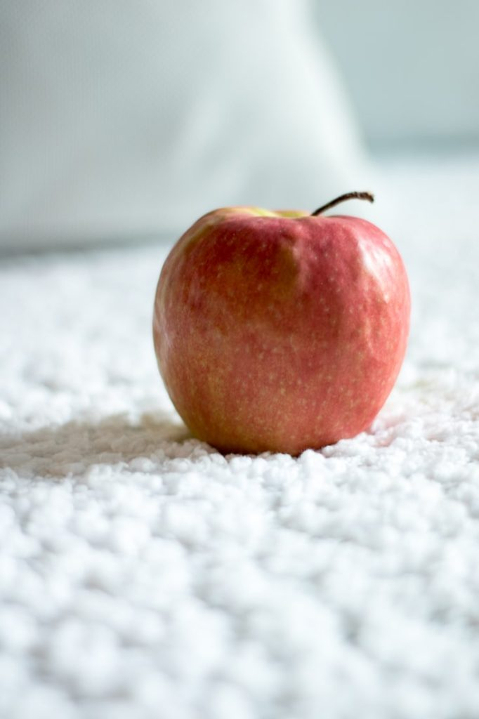 pink lady apple on the top of a white blanket.