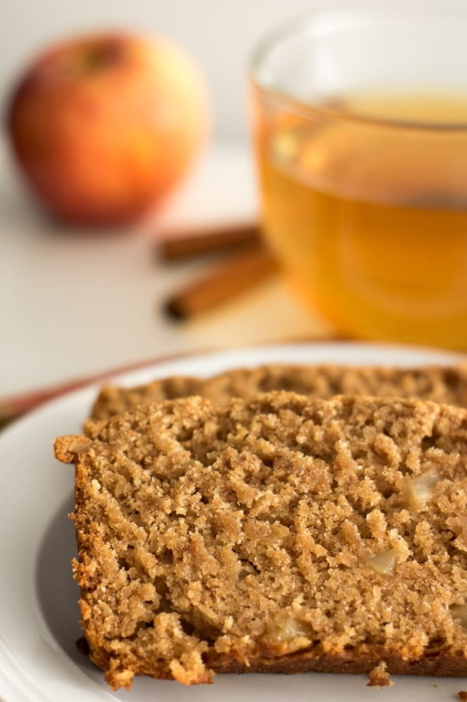 slices of apple cinnamon bread, with apple chunks and a cup of cinnamon apple tea with cinnamon sticks in the background
