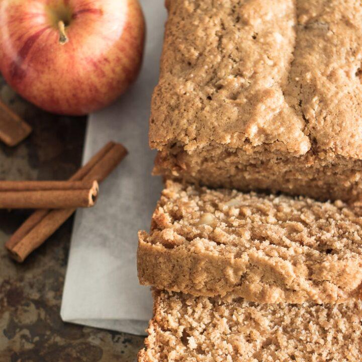 flat image of sliced apple bread, apple and cinnamon sticks.