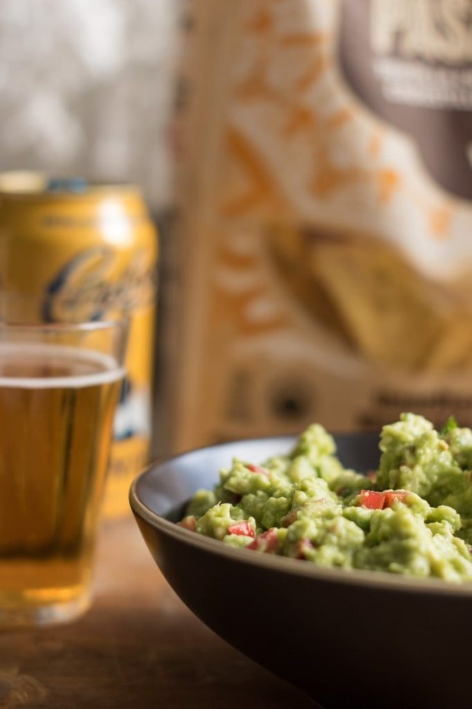Guacamole in a bowl, with beer and tortillas in the back