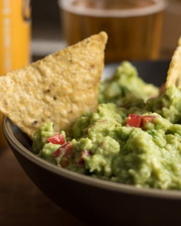Very green guacamole easily made for a game night, in a brown bowl with beer and tortillas