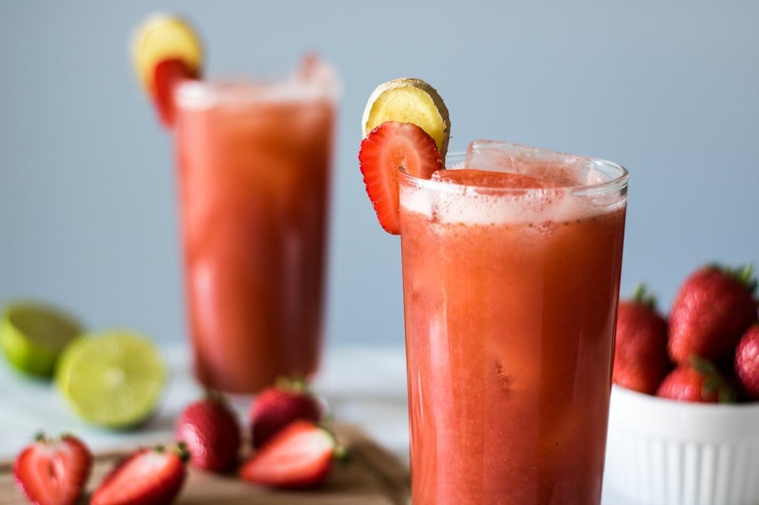 two cups of strawberry juice along strawberries and lime halves