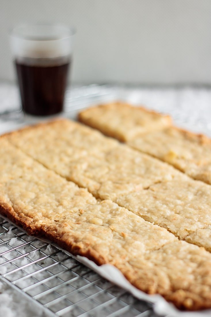 almond coconut shortbread bars and a cup of coffee, seen from above.