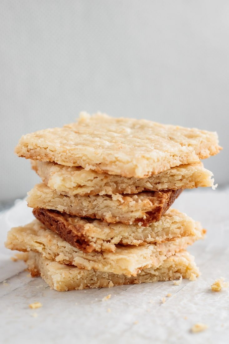 lots of almond coconut shortbread bars, stocked one above another, on parchment paper, with crumbs all over it, and a cup of coffee on the background.