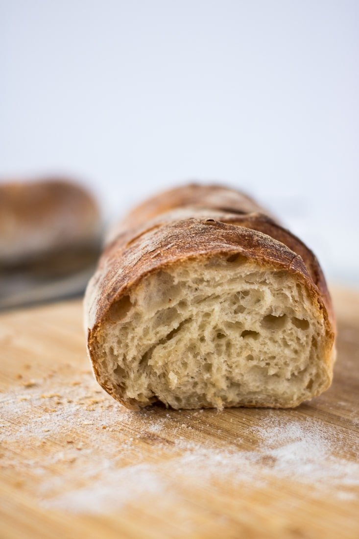 cut homemade french baguette showing its interior over wooden board