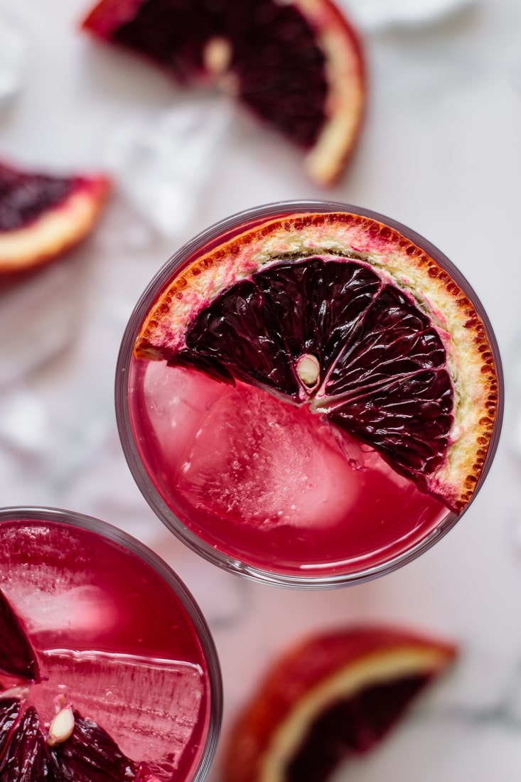 close up of blood orange lemonade in two glasses, with blood oranges on the top of the glass, ice, and slices of orange on the counter