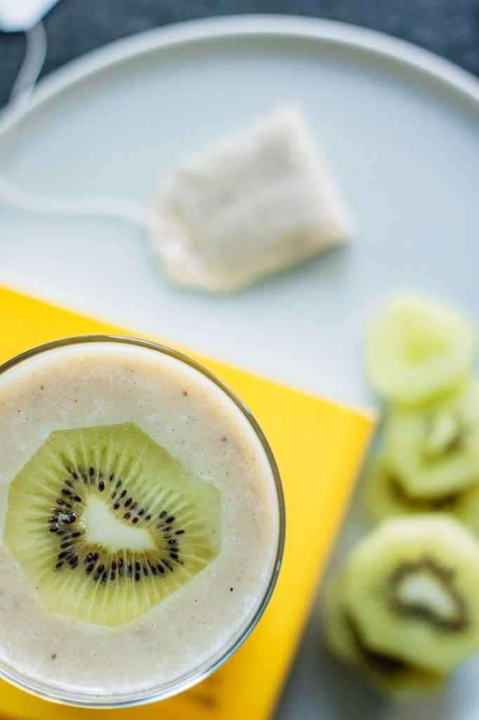 glass full of recipe with kiwi slices and a chamomile tea bag over a blue plate and yellow book cover