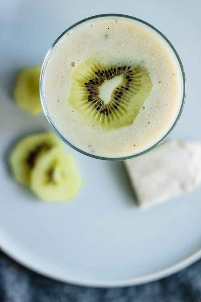 glass full of smoothie with kiwi slices and a chamomile tea bag