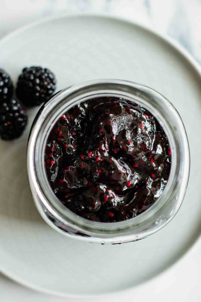 blackberry jam jar with three blackberries and a blue plate on the background