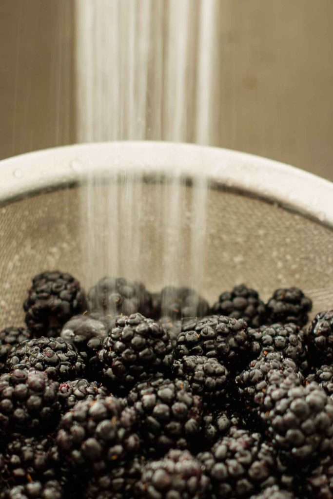 berries being washed over running water