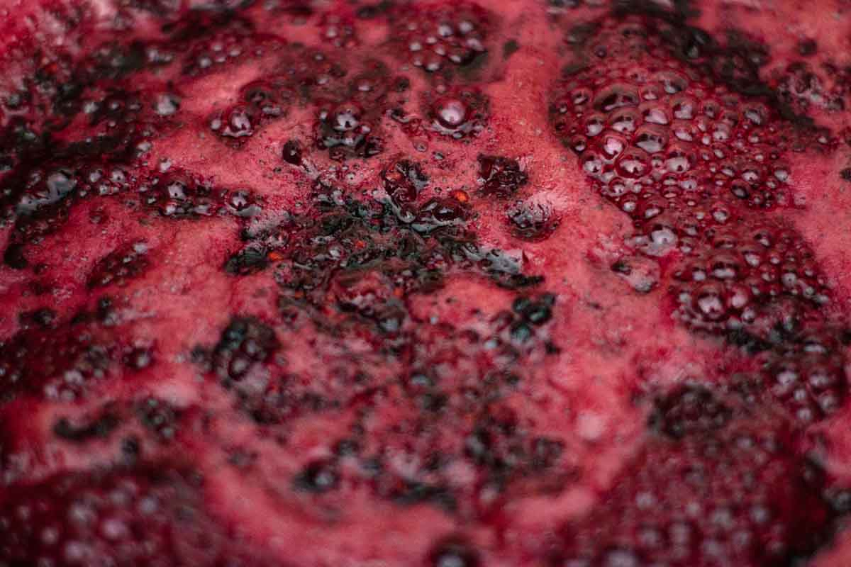 Blackberry jam cooking with foam.