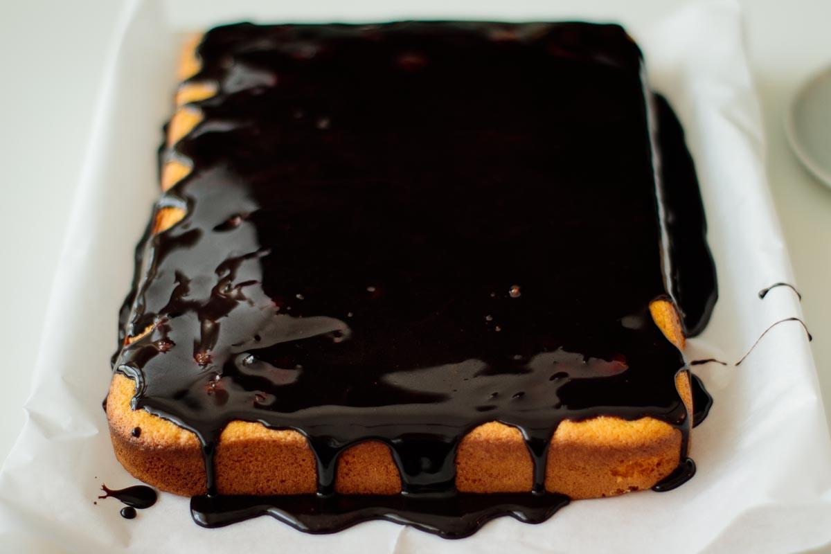 whole brazilian carrot cake topped with shiny chocolate glaze