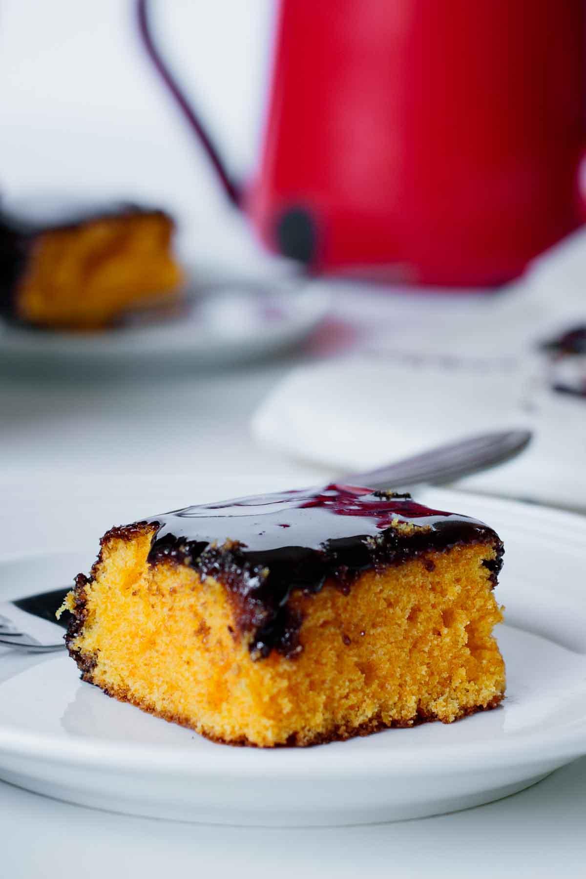 A piece of brazilian carrot cake with shiny chocolate glaze.