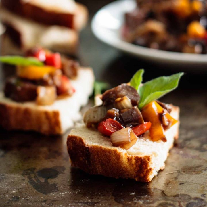 two caponata toasts with more caponata on the background