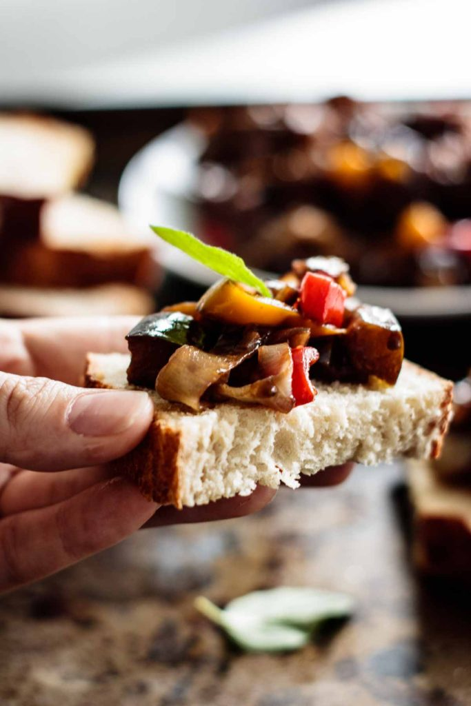 caponata over a sourdough toast held with caponata on the background