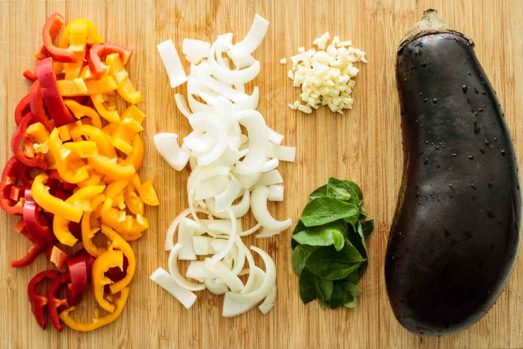 sliced bell peppers, oregano leaves, sliced onion, chopped garlic and an eggplant