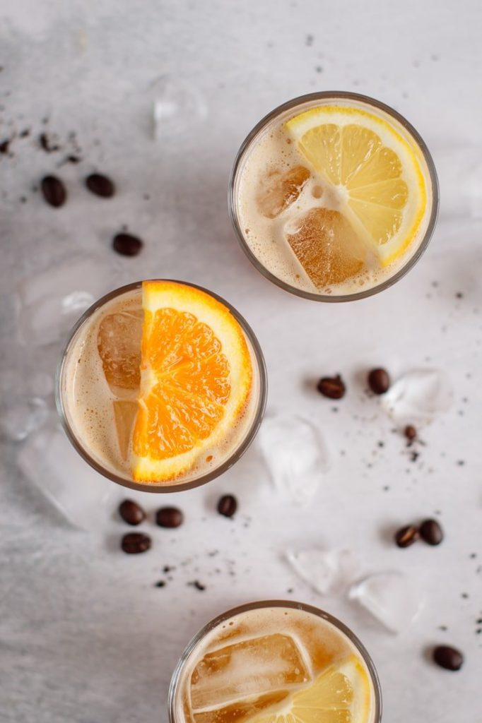 three glasses of coffee lemonade decorated with lemons and orange slices, filled with ice, coffee beans and ice on the background,