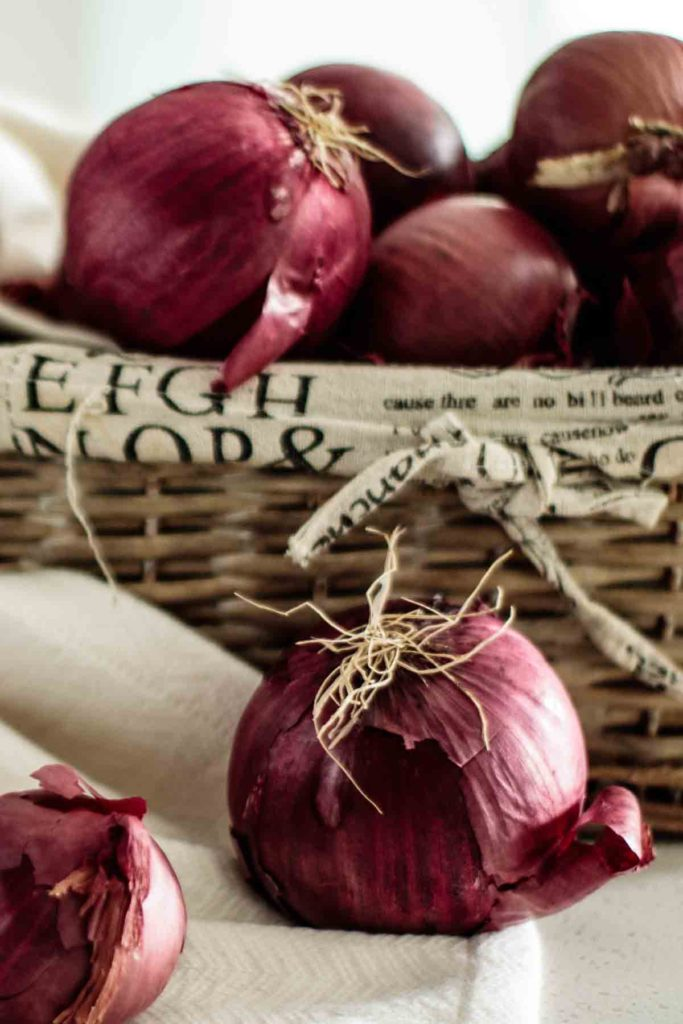 close up of a red onion, with red onions inside a box in the background