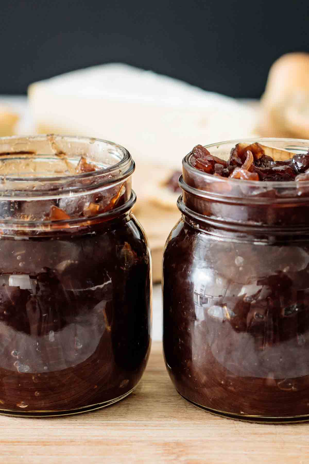 2 jars full of chutney over a wooden board.