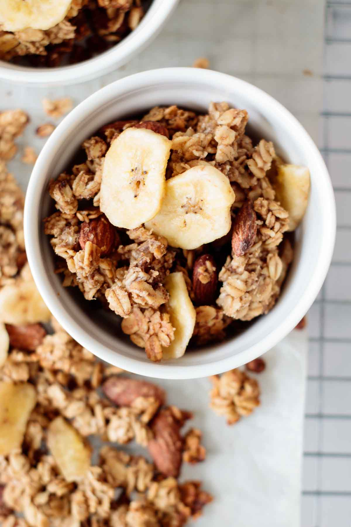 a bowl full of banana bread granola, with granola clusters on the side