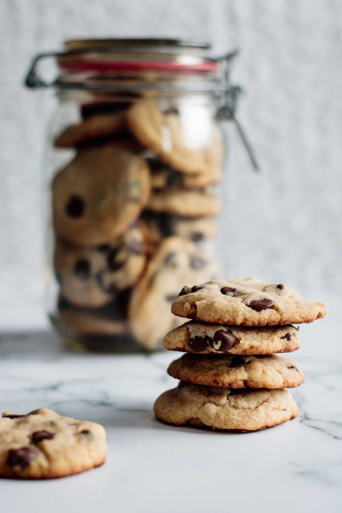 stack of chocolate chip cookies with cookies inside a jar in the background