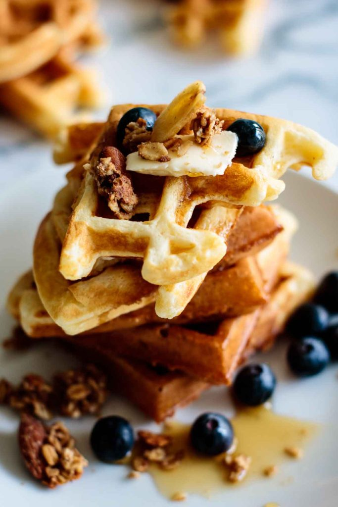 a stack of fluffy waffles with blueberries, maple and granola