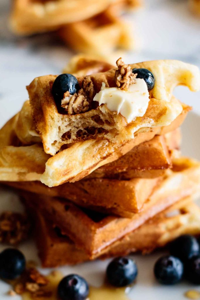 stack of waffle with close up on a half eaten waffle with maple syrup and blueberries