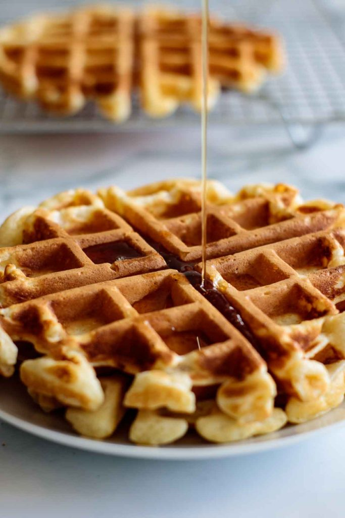 maple syrup dripping over fluffy waffles