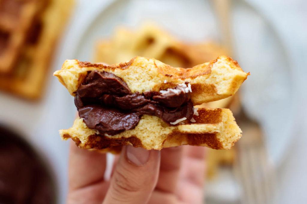 a waffle cut in half, with chocolate ganache