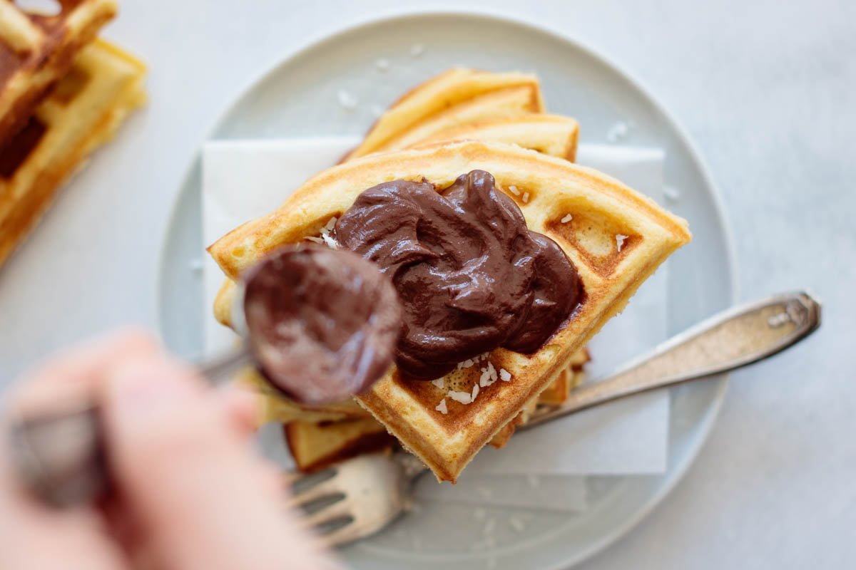 hand spreading chocolate ganache with spoon over a stack of waffles