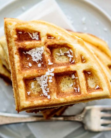 a stack of coconut flour waffles, with coconut flakes on the top, fork on the side and napkin