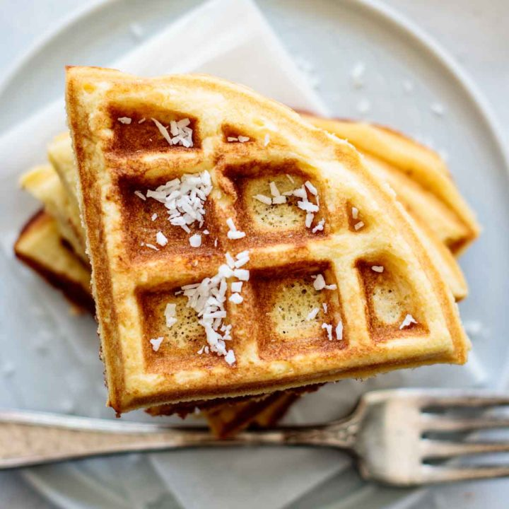 A stack of coconut flour waffles, with coconut flakes on the top.