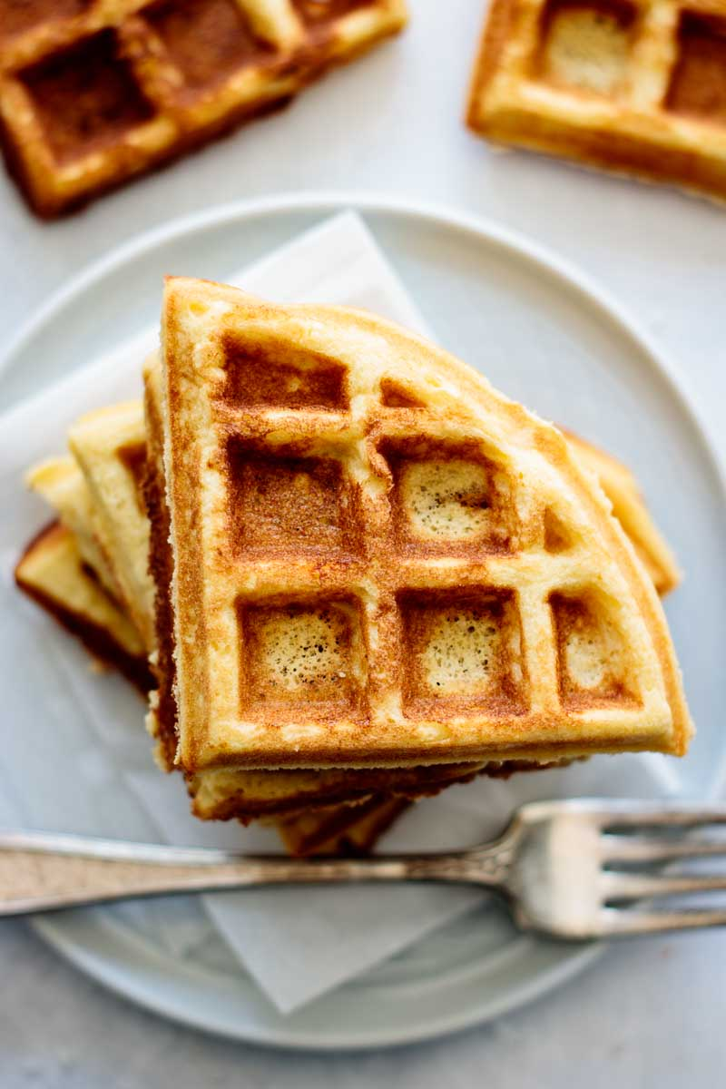 a stack of coconut waffles on a plate, with napkin and fork on its side