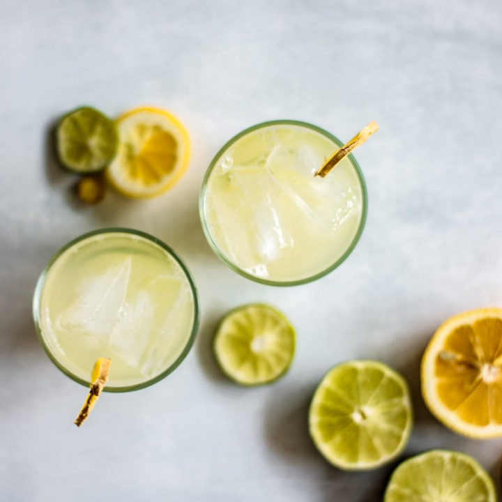 2 glasses of ginger honey iced tea seen from above, with slices of lemon and lime in the background