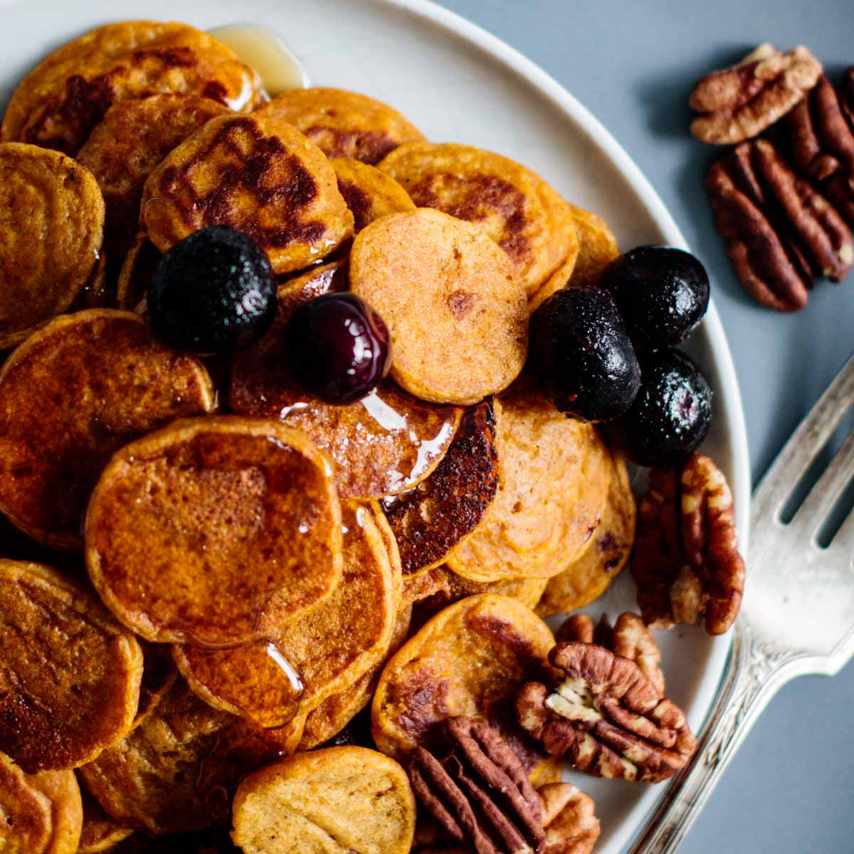 half of a plate full with sourdough pumpkin pancake cereal, pecan, maple syrup and blueberries, fork on the side.