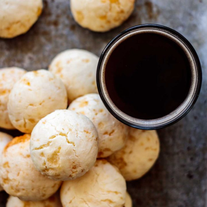 a stack of cheese bread with a cup of black coffee