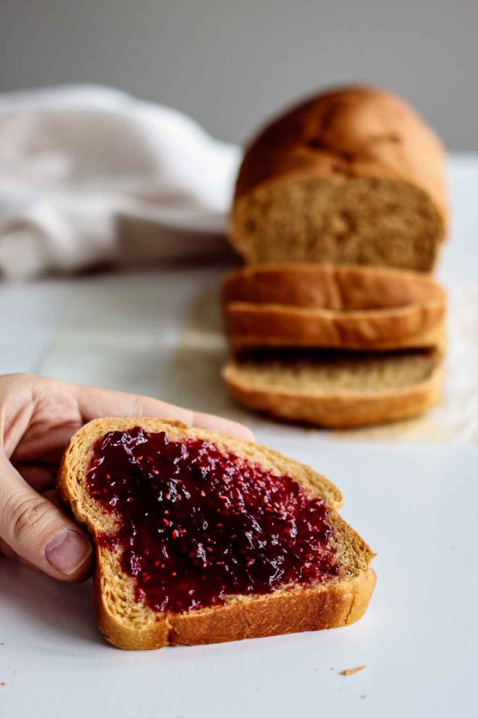 hand holding a slice of bread with raspberry jam