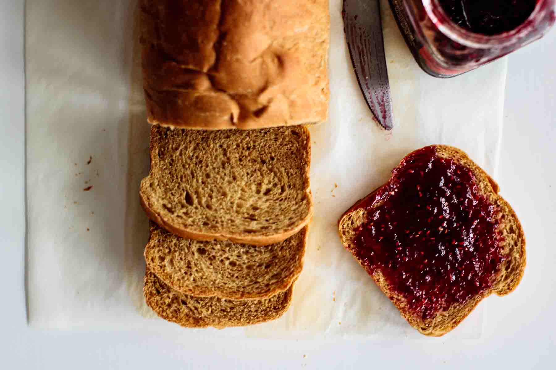 slice of bread with raspberry jam, bread, jam and knive