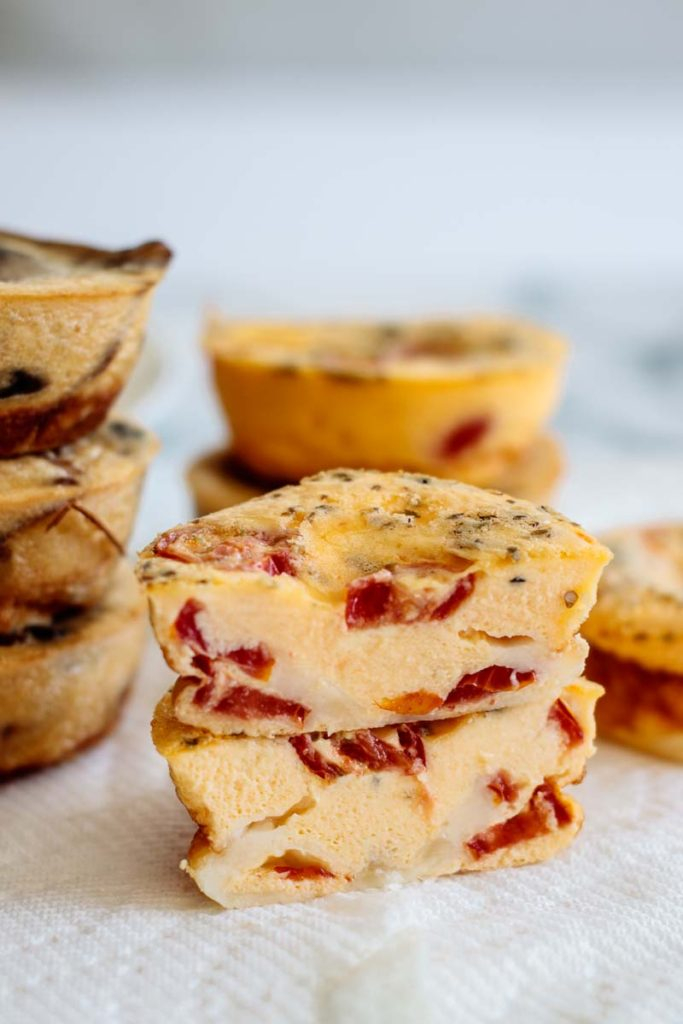 the inside of a breakfast pizza egg muffin cup, showing tomatoes and melted cheese
