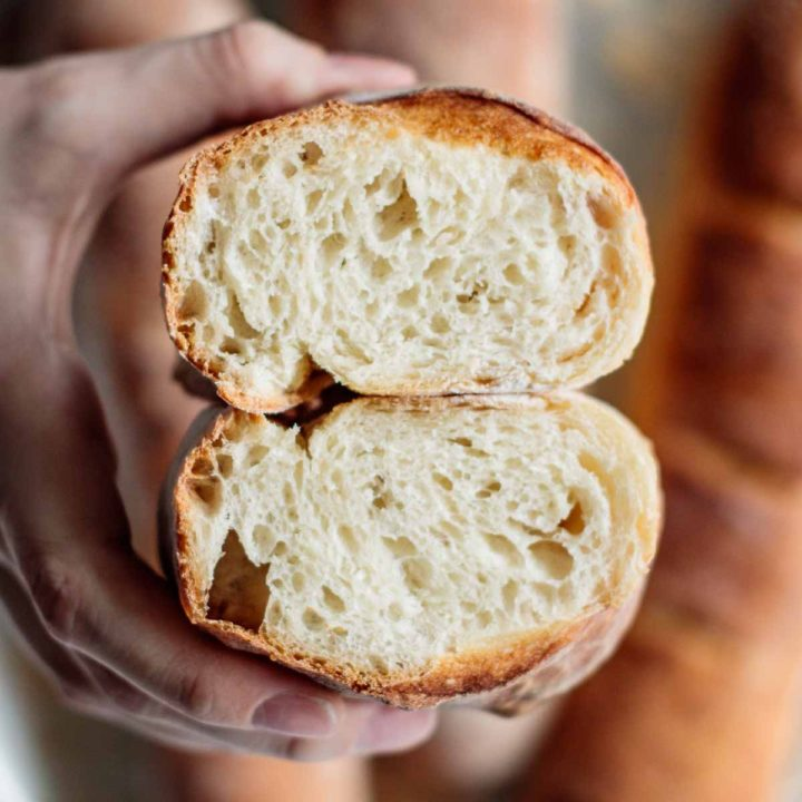 french baguette cut in half, showing its interior, soft and chewy, with baguettes in the background