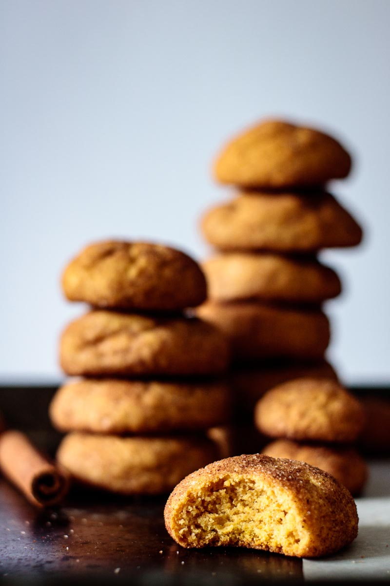 half bitten cookie with cookie tower on the background, with a cinnamon stick