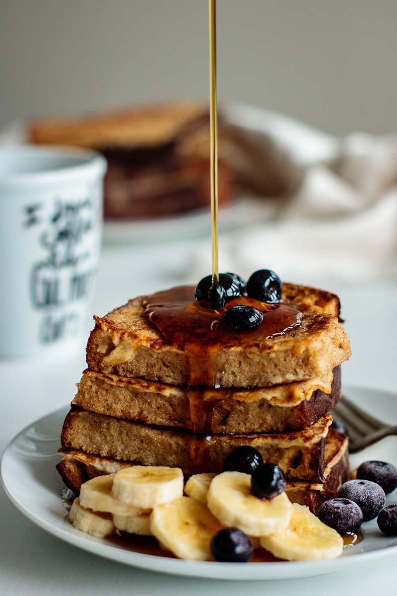 maple syrup drizzling on top of a sourdough french toast stack