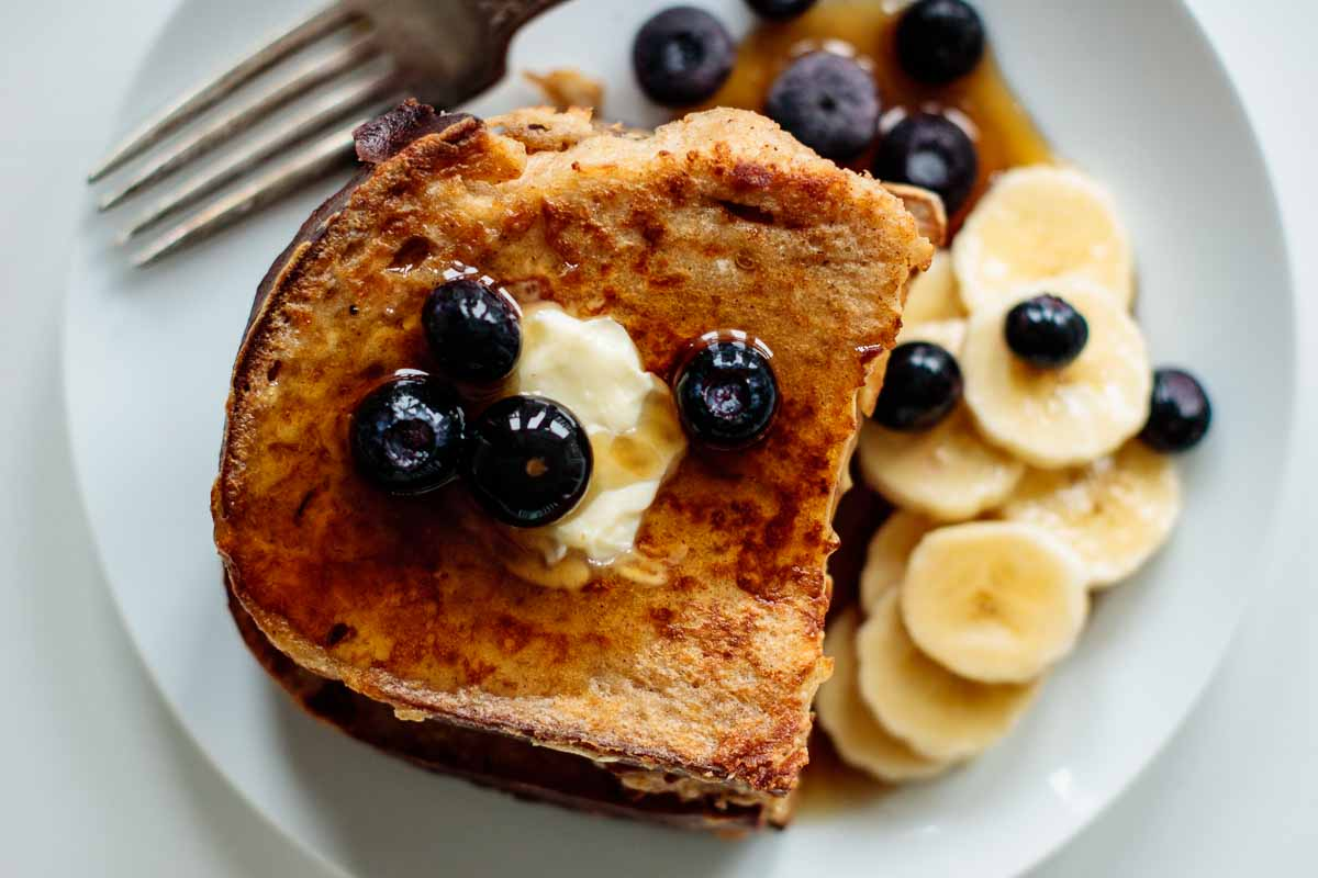 sourdough french toast with butter, berries, banana and maple syrup seen from above