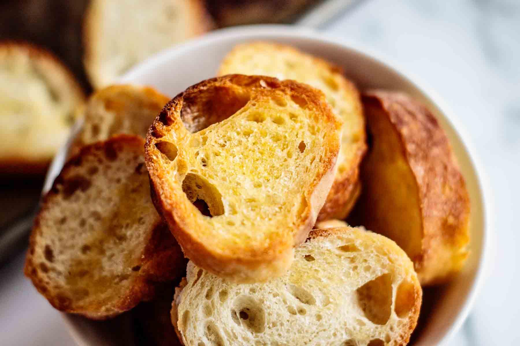 A bowl full of golden baked crostini.