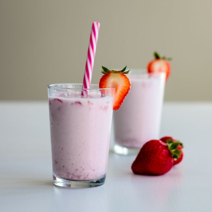korean strawberry milk on a decorated glass with pink straw and strawberry on the side