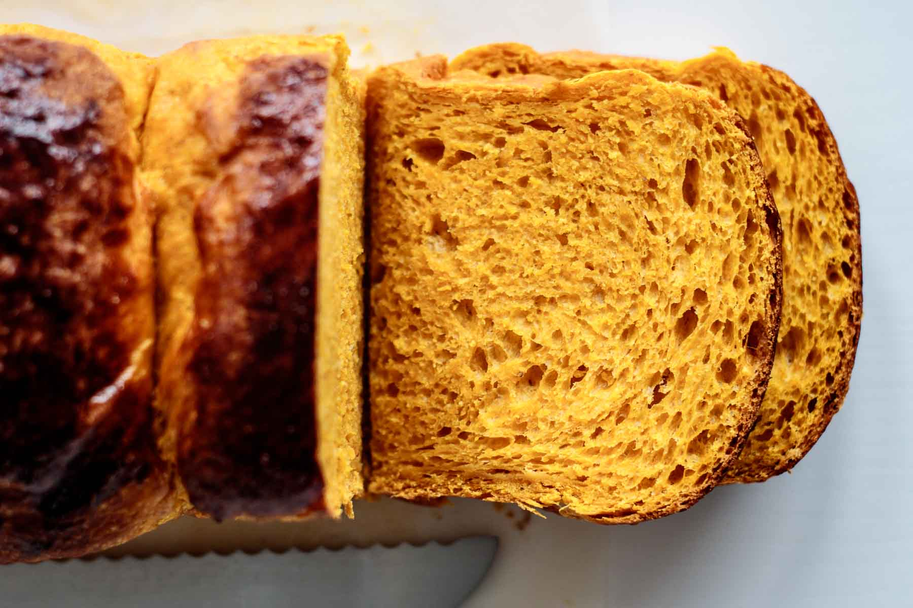 close up on sliced pumpkin brioche, showing its soft and bright orange crumb