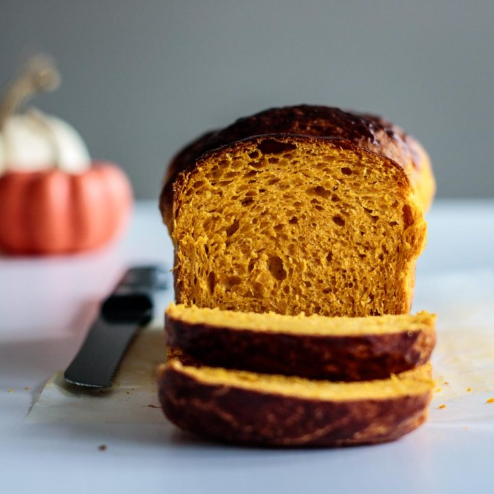 sliced pumpkin bread with pumpkins on the background
