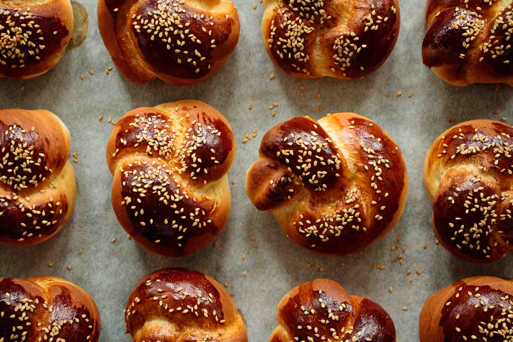 a tray full of baked challah rolls